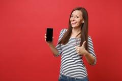拿着有空白黑空的屏幕的美丽的年轻女人陈列赞许画象手机隔绝在明亮 免版税库存照片