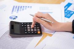 拿着笔的女实业家和分析与计算器的销售计划在木书桌上在办公室 背景概念饮食金黄蛋的财务 免版税库存图片