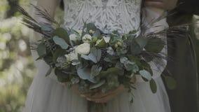 拿着美丽的白色婚姻的花花束的鞋带礼服的新娘 股票视频