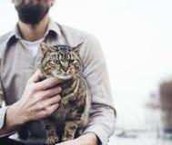 拿着猫的人 免版税图库摄影