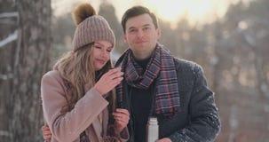 拿着热的茶杯的愉快的夫妇在冬天环境美化 在爱的年轻夫妇在一寒假,站立在旁边 股票录像