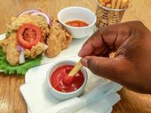 拿着薯条的非洲人的手,浸洗在番茄酱-吃食物在餐馆;鸡翅和调味汁 免版税库存照片