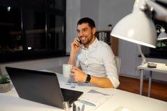 拜访智能手机的商人在夜办公室 图库摄影