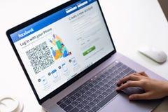 曼谷,泰国- 2019年3月13日:手按在膝上型计算机,社会媒介的Facebook屏幕 免版税图库摄影