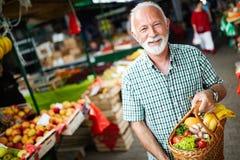 更旧的愉快的男性采购员藏品篮子用水果和蔬菜 库存照片