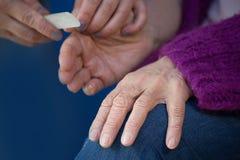 更老的资深妇女用接受家庭温泉治疗修指甲的关节炎手 库存图片