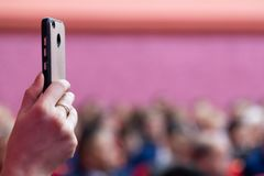 智能手机在一只女性手上 观众席 被弄脏的桃红色背景 照片或录影在一个手机 直播在帮助下 免版税库存照片