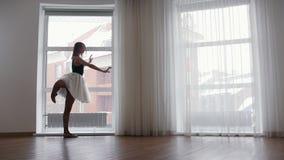 支持窗口和训练她的舞蹈的年轻女人芭蕾舞女演员 股票视频