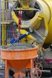 新维德,德国- 2019年2月1日:卡车司机填写灰浆在他的灰浆卡车外面对水泥筒仓 图库摄影