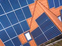 新的现代住宅房子村庄空中顶视图与蓝色发光的太阳照片流电盘区系统的在屋顶 可延续 库存照片