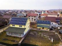 新的现代住宅房子村庄空中顶视图与蓝色发光的太阳照片流电盘区系统的在屋顶 可延续 库存图片