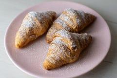 新鲜的新月形面包用在板材的糖 免版税库存照片