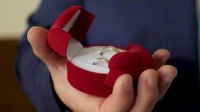 新郎拿着有结婚戒指的箱子在他的提案的手上对他心爱 创建新的家庭 特写镜头 股票录像