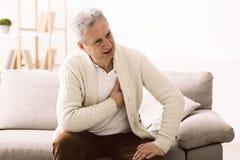 攻击重点保留人 遭受胸口痛的老人 免版税库存照片