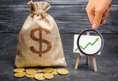 放大镜看绿色箭头在图和一个袋子与金钱 增长的赢利和收支的概念 免版税库存照片