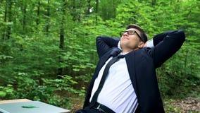 放松在勤勉天以后的高兴的商人在美丽的绿色森林里 免版税图库摄影