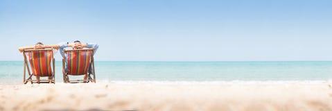 放松在椅子海滩的年轻夫妇 免版税库存照片