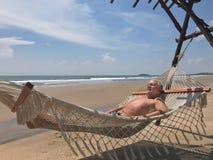 放松在海海滩的吊床的人 库存照片