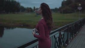放松的少女,在平衡公园的听的音乐 站立在水附近 股票录像