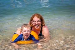 放置在水中的母亲和孩子特写镜头画象看在照相机 免版税库存照片
