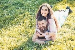 放置在草春日的男人和妇女 春天休闲概念 在放置在有雏菊的草甸的愉快的面孔的夫妇 免版税库存图片