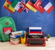 政治,新闻和教育俄罗斯的概念-红色打字机,旗子和其他国家,背包,书,文具 免版税库存图片
