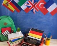 政治,新闻和教育德国的概念-红色打字机,旗子和其他国家,背包,书,文具 库存照片