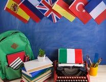 政治,新闻和教育意大利的概念-红色打字机,旗子和其他国家,背包,书,文具 免版税库存图片