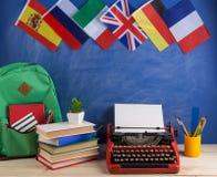 政治,新闻和教育西班牙的概念-红色打字机,旗子,法国、英国和其他国家,背包,书 库存照片