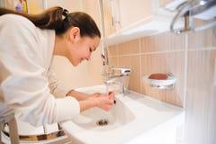 洗她的面孔的年轻女性在卫生间里 免版税库存照片