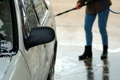 洗涤一辆白色汽车 妇女在背景中 免版税库存照片