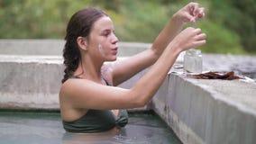 洗热量浴和收集面膜的愉快的妇女愈合泥 享受在自然的年轻女人温泉 股票视频