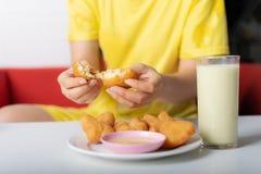 撕毁油煎的小圆面包的妇女的手在杯在桌上的豆浆附近 库存图片