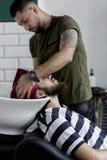 理发师抹人的头发与毛巾在理发店 免版税库存照片