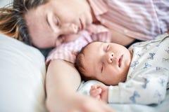 睡觉在床上的新生儿和母亲画象,一起休息 图库摄影