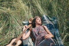 睡觉在被割的草的年轻嬉皮妇女 免版税图库摄影