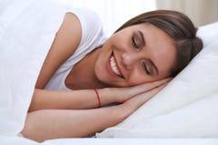 睡觉美丽的年轻和愉快的妇女,当舒适地在床上和有福地微笑时 免版税库存图片