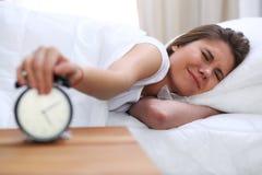 睡觉美丽的年轻和愉快的妇女,当舒适地在床上和有福地微笑时 库存照片