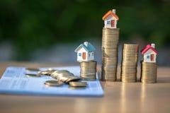 硬币和财政决算或储蓄账户帐薄在桌、事务、财务、攒钱、物产梯子或者抵押贷款上 免版税图库摄影