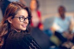 确信地微笑年轻女实业家的戴着眼镜,当站立在有工作在时的同事的一个办公室 库存图片