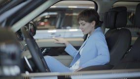 礼服蓝色衣服的年轻俏丽的妇女汽车的开门并且坐在它里面在前面乘客座位 现代的女孩 股票录像