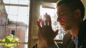 祈祷的年轻人的画象在阳光下 坐由在一个老大厦的窗口 影视素材