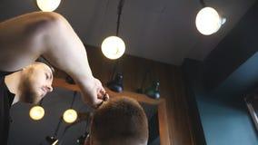 移动式摄影车梳他的顾客的头发的被射击男性美发师在时髦理发店 得到年轻人的背面图他 股票视频