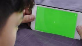 移动式摄影车被射击孩子在他的手上拿着一个电话有色度关键大模型的一个绿色屏幕的 股票录像
