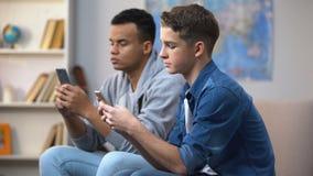 移动智能手机,小配件瘾的非裔美国人和白种人青少年 股票录像