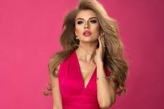 秀丽女服桃红色礼服,在桃红色墙壁 库存图片