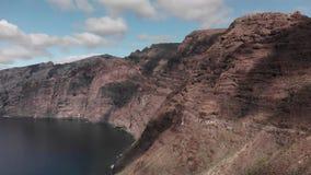 空中射击 一块巨大的黑红色火山岩是在海洋的大海的一座山 蓝天 金丝雀 股票视频