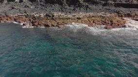 空中射击 有起泡沫的波浪的蓝色和绿松石海洋 火山的岸是山海滩的质地表面 股票视频