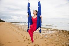 空中瑜伽或反地心引力的瑜伽 年轻女人实践的飞行瑜伽asana户外 免版税库存照片