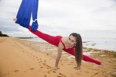空中瑜伽或反地心引力的瑜伽 年轻女人实践的飞行瑜伽asana户外 免版税库存图片